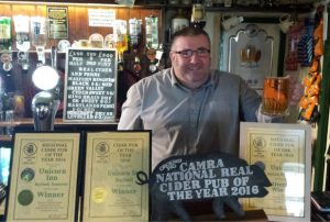 Richard Cummins, landlord at The Unicorn Inn in Bayford near Wincanton, surrounded by his awards presented by the Campaign for Real Ale (CAMRA)